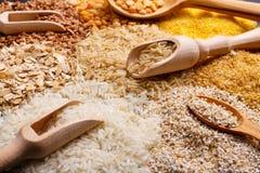 Miserables ed i cucchiai hanno riempito di cereali sui precedenti di un mucchio del primo piano dei cereali Fotografia Stock Libera da Diritti