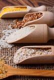 Miserables et une cuillère remplie des céréales sur une serviette à partir d'une toile de jute se situent dans une rangée et sont Photographie stock libre de droits