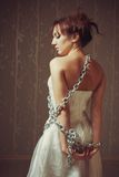 Misery. Portrait of pretty young bride bounded by chains Royalty Free Stock Photos