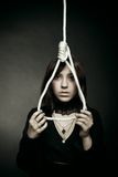 Misery. Sad girl with gallows over dark background Royalty Free Stock Photography