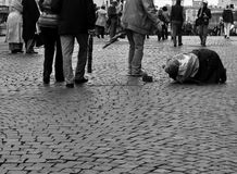 Misery. A mendicant begging in a square of Rome. Pedestrians ignore him. Black and white Royalty Free Stock Image