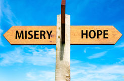 Misery versus Hope. Wooden signpost with two opposite arrows over clear blue sky, Misery versus Hope messages Royalty Free Stock Images
