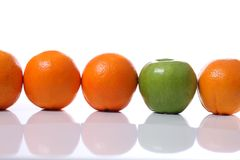 Misfit. Row of oranges infiltrated by a green apple Royalty Free Stock Photo