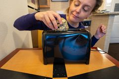 Misguided woman attempts to stuff a large blueberry scone into a small toaster slot, meant for bread.  stock photography