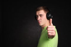 Misic ic cool. Man in headphones shows thumb up Royalty Free Stock Image