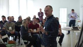 Misk, Λευκορωσία - 23 Ιουλίου 2018: Το καυκάσιο peaker σε ένα πουκάμισο καρό μιλά στο στάδιο πέρα από την οθόνη παρουσίασης φιλμ μικρού μήκους