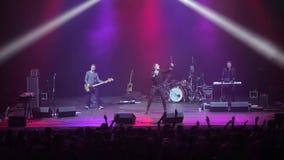 Misk, Λευκορωσία - 15 Μαΐου 2017: Όμορφος καυκάσιος τραγουδιστής με μακρυμάλλη και ορχήστρα ροκ που εκτελεί τη μουσική στη σκηνή  απόθεμα βίντεο