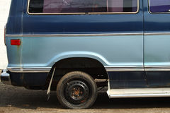 Mismatch. A very small tire on a old blue van Royalty Free Stock Photography