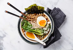 Miso Ramen noodles with egg, enoki and pak choi. Miso Ramen Asian noodles with egg, enoki and pak choi cabbage in bowl on white marble background Stock Photos