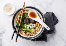 Miso Ramen noodles with shiitake, tofu and pak choi. Miso Ramen Asian noodles with shiitake, tofu and cabbage pak choi in bowl on white marble background Stock Photo