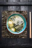 Miso soup in blue bowl on dark rustic background, top view Royalty Free Stock Photography