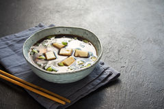 Miso soup. Japanese miso soup in ceramic bowl on black stone table, copy space. Asian miso soup with tofu Stock Photo
