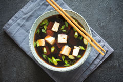 Miso soup. Japanese miso soup in ceramic bowl on black stone table, copy space. Asian miso soup with tofu Royalty Free Stock Images