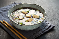Miso soup. Japanese miso soup in ceramic bowl on black stone table, copy space. Asian miso soup with tofu Stock Image