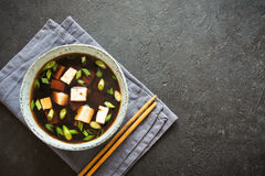 Miso soup. Japanese miso soup in ceramic bowl on black stone table, copy space. Asian miso soup with tofu Royalty Free Stock Photography