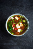 Miso soup. Japanese miso soup in ceramic bowl on black stone table, copy space. Asian miso soup with tofu Stock Photos