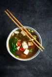 Miso soup. Japanese miso soup in ceramic bowl on black stone table, copy space. Asian miso soup with tofu Royalty Free Stock Image