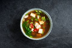 Miso soup. Japanese miso soup in ceramic bowl on black stone table, copy space. Asian miso soup with tofu Royalty Free Stock Photo