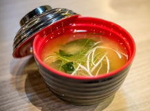 Miso soup in red blow. Miso soup on the wood table and red blow Royalty Free Stock Images