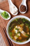 Miso soup in a white bowl and ingredients vertical top view. Japanese miso soup in a white bowl and ingredients in a spoon on a table close-up. vertical top view Royalty Free Stock Images