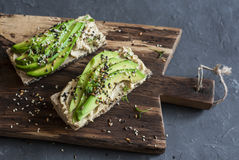 Miso tahini avocado sandwich on wooden cutting board on a dark background. Royalty Free Stock Photography