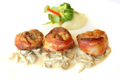 Mięso w bekonie z garnirunkiem, wyśmienity jedzenie Zdjęcie Royalty Free