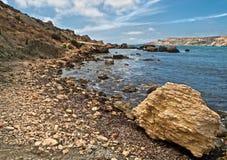 Misplaced. Fallen limestone boulders near the coast in Malta Stock Photos