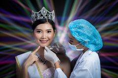 Miss Beauty Queen Pageant Contest with Diamond crown sash is che. Cked up by Beautician Doctor and recommend consult before Syringe injection skincare medical stock photo