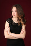 Miss with crossed arms. Close up. Dark red background Royalty Free Stock Image