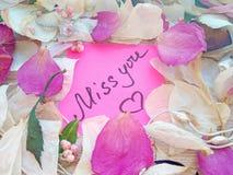 Miss dig meddelandet på rosa klibbig anmärkning med torra ros- och orkidéblommakronblad och den silversmyckencirkeln och kedjan p arkivbild