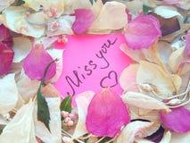 Miss dig meddelandet på rosa klibbig anmärkning med torra ros- och orkidéblommakronblad och den smyckencirkeln och kedjan på träb arkivfoto
