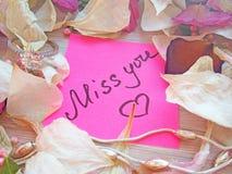 Miss dig meddelandet på rosa klibbig anmärkning med torra ros- och orkidéblommakronblad och försilvra den smyckencirkeln och kedj arkivfoton