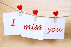 Miss dig text på klistermärkear som hänger på hjärtaformben royaltyfria bilder