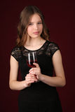 Miss in dress holding glass of wine. Close up. Dark red background Stock Image
