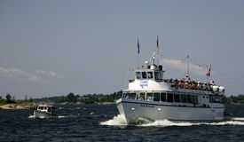 Miss Midand. Miss Midland a popular tour boat cruising in the islands of Georgian Bay, Ontatario, Canada. It is crouded with tourists. A small boat is beside the Royalty Free Stock Photography
