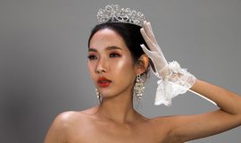 Miss Pageant Beauty Contest in white gray sequin. Portrait of Miss Pageant Beauty Contest in white gray sequin Evening Ball Gown dress sparkle light Silver stock image