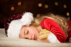 Miss santa. Little miss santa asleep with a gift in her hand Stock Images