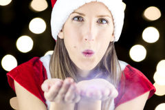 Miss Santa blowing magic wish dust at you Stock Images