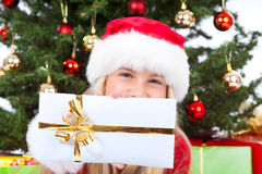 Miss santa holding a gift and smiling. Miss santa smiling and holding gift in front of christmas tree in background Royalty Free Stock Photo