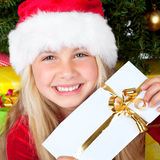 Miss santa holding a gift and smiling Stock Photo