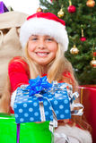 Miss santa holding a gift and smiling Royalty Free Stock Image