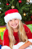Miss santa holding a gift and smiling Royalty Free Stock Photo