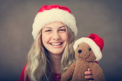 Miss santa holding a teddy with santa hat Stock Image