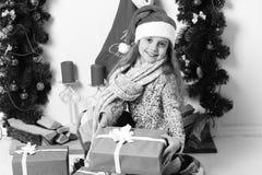 Miss Santa i röd hatt rymmer blåa gåvaaskar fotografering för bildbyråer