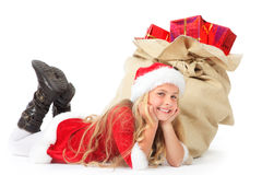 Miss santa lying beside christmas sack smiling. Little miss santa lying beside a filled christmas sack on white Royalty Free Stock Images