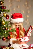 Miss santa opening a gift. Little miss santa sitting past the christmas tree and opening a gift Royalty Free Stock Photography