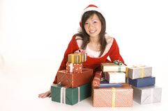 Miss Santa and Presents. A cute asian female santa sits with a pile of presents Stock Photography