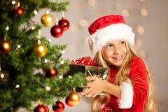 Miss santa shaking a gift Royalty Free Stock Images