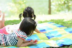 Two Kids laying down in the park Royalty Free Stock Image