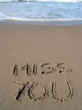 MISS YOU!. Words miss you written on the sand Royalty Free Stock Photos